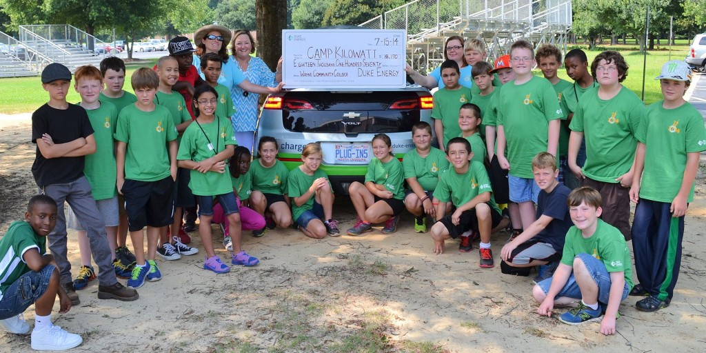 Millie Chalk, a community relations manager for Duke Energy (left side, beside car) presents a donation from Duke Energy Foundation to campers at Wayne Community College's Camp Kilowatt and two of their leaders, WCC Instructor and Camp Kilowatt Founder Angela Wall and Camp Counselor Julie Heath.