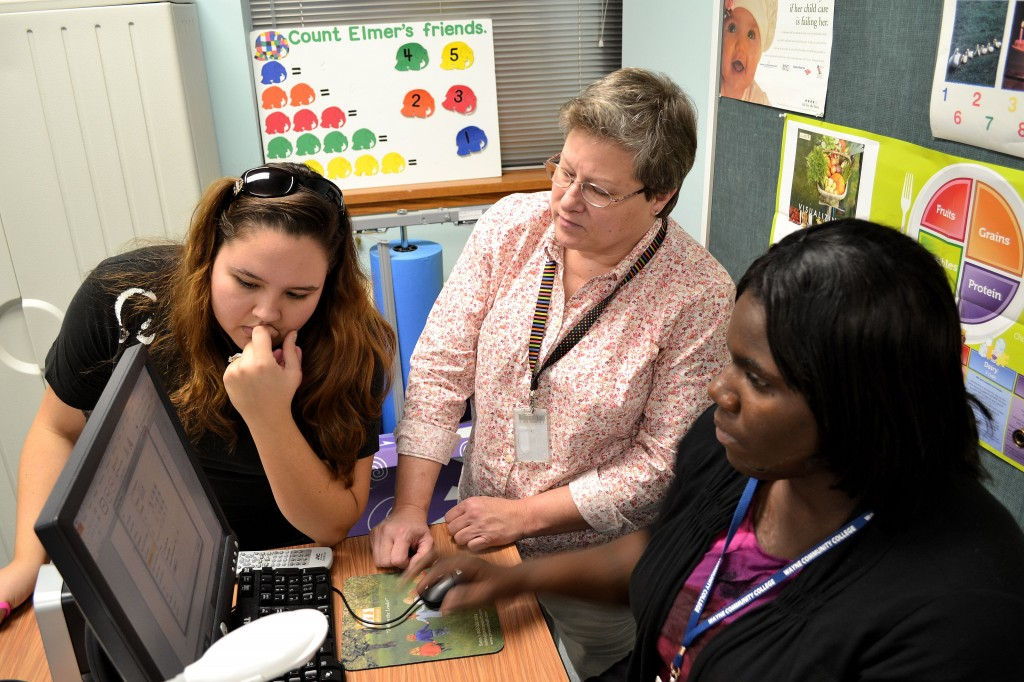 WCC Early Childhood Education Instructor Sherry Granberry (center) advises students Allison Thrower (left) and Diana Ogbondah on a class project.
