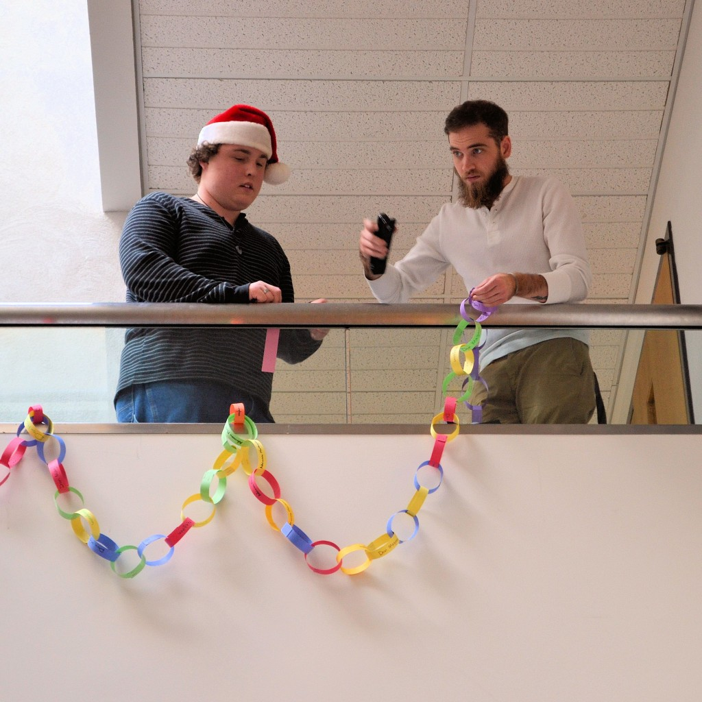 WCC students Jacob Pawvluk (left) and Caleb Grant hang paper-link chain along the stairs in the Atrium of the Wayne Learning Center. Each link signifies a 50 cent donation to the Link Up for the Philippines project.
