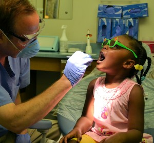 Dr. Kevin Buchholtz checks Sydney Singleton's teeth during a kindergarten screening.