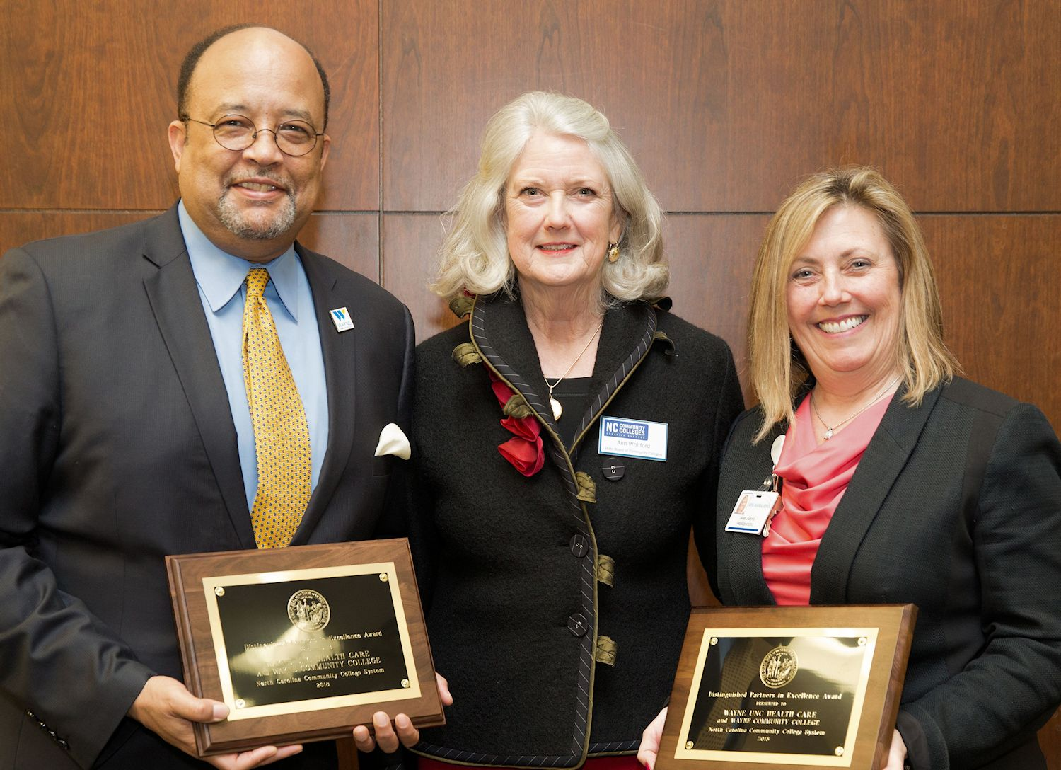 State Board of Community Colleges member standing with WCC President and Wayne UNC Health Care President and CEO, both of which have .Distinguished Partners in Excellence Award plaques in their hands.