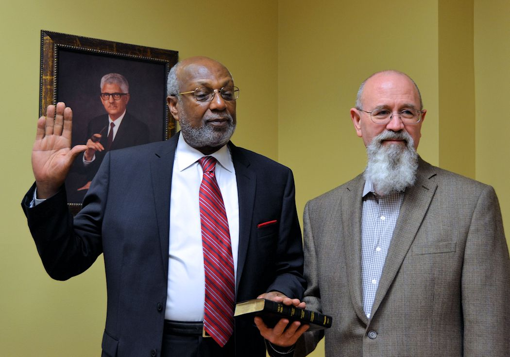 Jimmie Ford holding up right hand and placing left hand on Bible held by Don Magoon as he takes the oath of office.